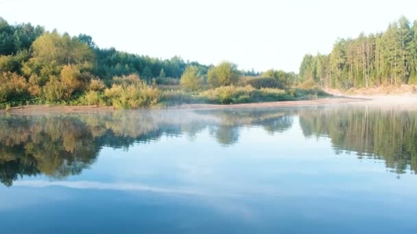 Mist over the river. Autumn beautiful landscape of forest is reflected in the water on the riverbank.