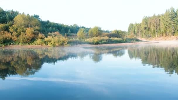 Köd a folyón. Őszi erdő gyönyörű tája tükröződik a vízben, a folyóparton.
