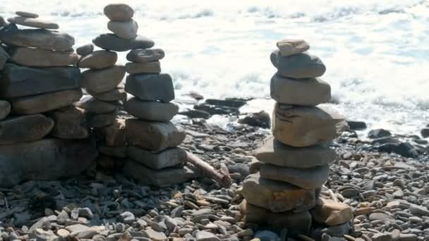 Stone towers on the seashore. Waves on the rocks beach.
