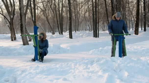 Muž a žena v modré bundy se účastní simulátory v zimě parku. Pohled zepředu.