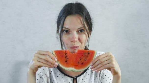 brünette Frau essen saftige Wassermelone auf weißem Hintergrund.