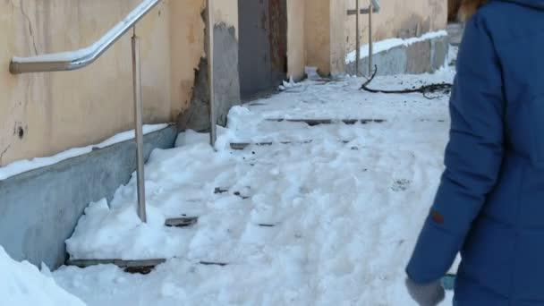 Kluzké schody. Nelze rozpoznat žena v bundu procházky zasněženou schodiště