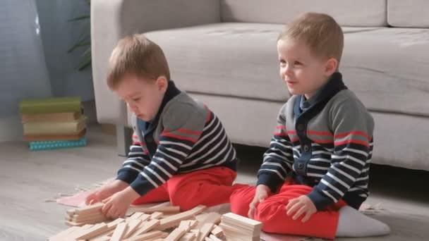 Dvojčata kluky bratři jsou budova z dřevěných kostek, sedí na pohovce v pokoji na podlaze.