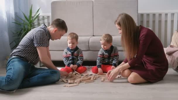 Rodinné máma, táta a dvě dvojčata hrát společně vytváří z dřevěných kostek na podlaze.