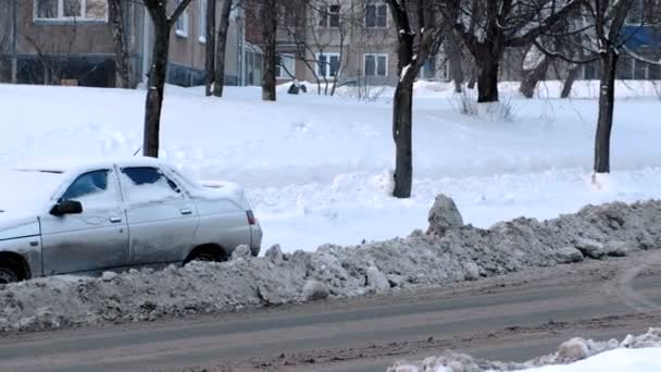 Snow-covered car on the side of a snowy road.