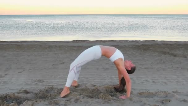 Young woman doing yoga stretching Chakrasana Wheel Pose on the sandy beach at sunrise.