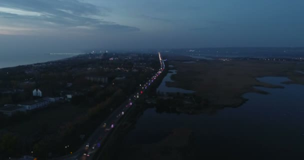 Beautiful night view of coastal city with roadway and wet meadows.