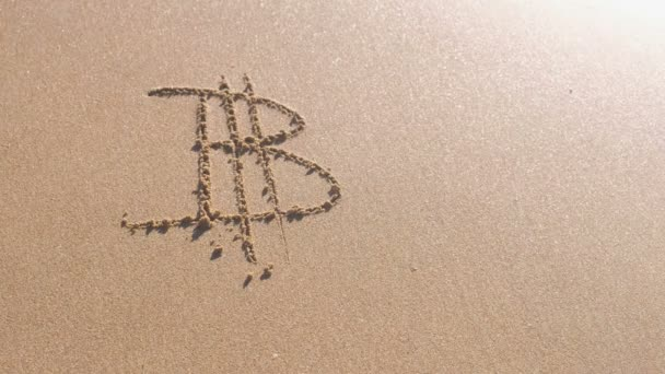 Bitcoin sign written in the sea sand. Waves washed away the inscription.