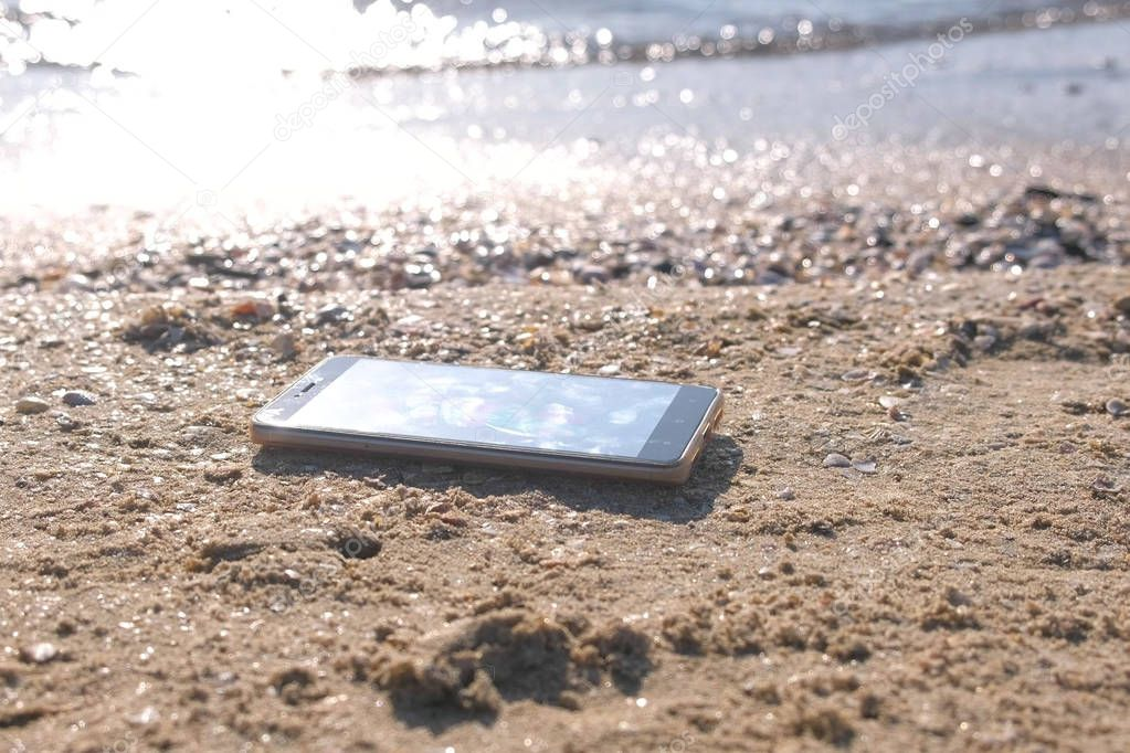 Mobile phone on the sandy sea beach with waves.