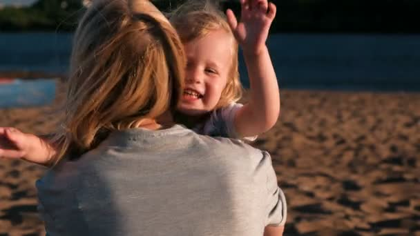 Beautiful happy blonde mom and daughter cuddling and speaking on the beach at sunset.