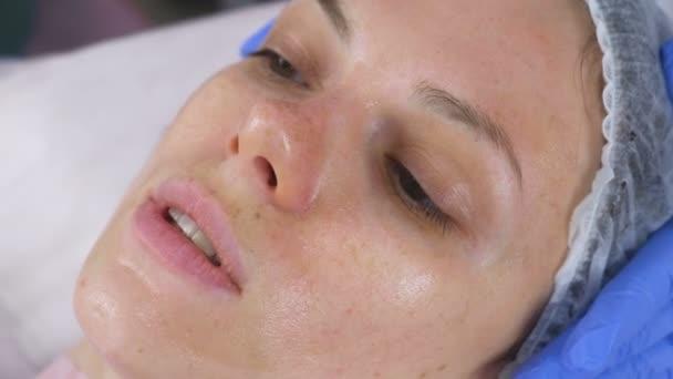Womans szembenéz-val egy áttetsző maszk az arcán. Arckezelés közül választhatnak a kozmetikus.