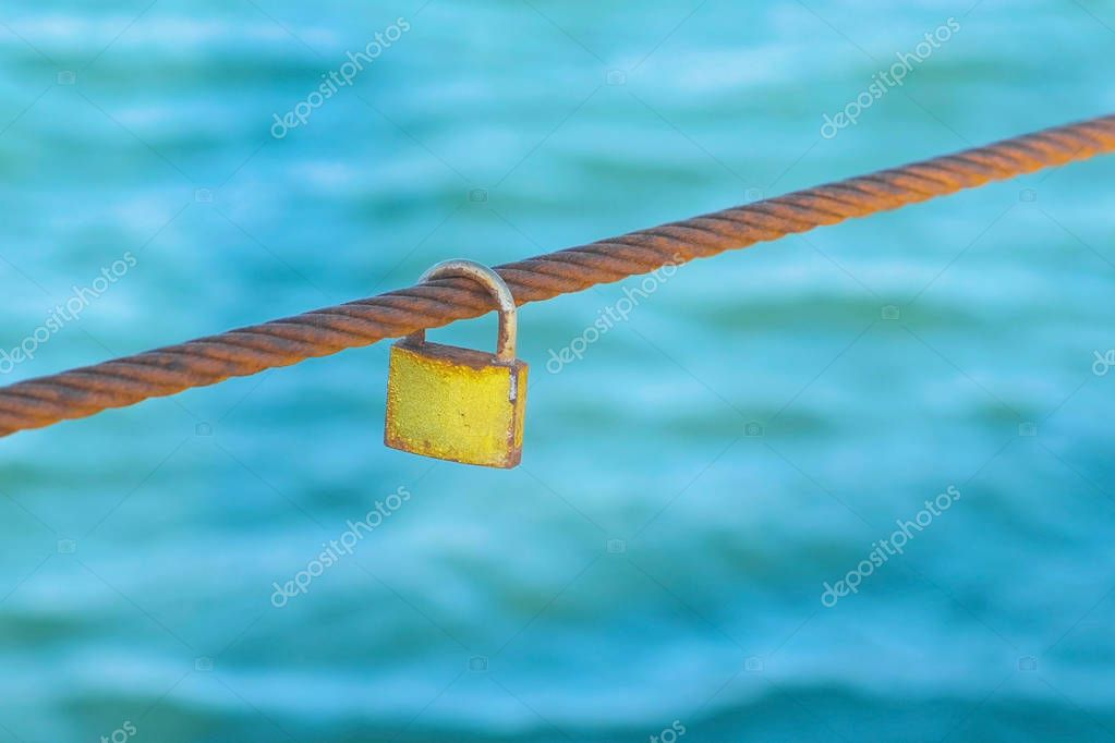 Rusty Padlock hanging on a iron wire on the sea water background.