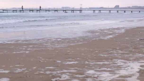 Turisté jsou fotografoval na molo v moři. Bouře na moři velké vlny. Krásná krajina při západu slunce