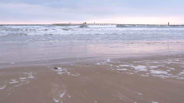Velké bouřlivé vlny v moři. Krásná krajina s molo, písečné pláže a pobřežní město na pozadí při západu slunce.