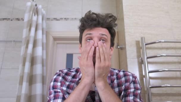 Müde geweckt Mann mit einem Kater Gähnen im Badezimmer, begibt sich in Ordnung, Stöcke Flecken unter den Augen.