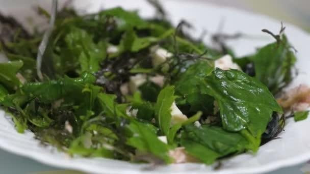 Insalata di close-up verdi, olive e pesce su un piatto. Cibo sano