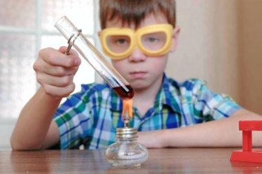 Experiments on chemistry at home. Boy heats the test tube with red liquid on burning alcohol lamp.