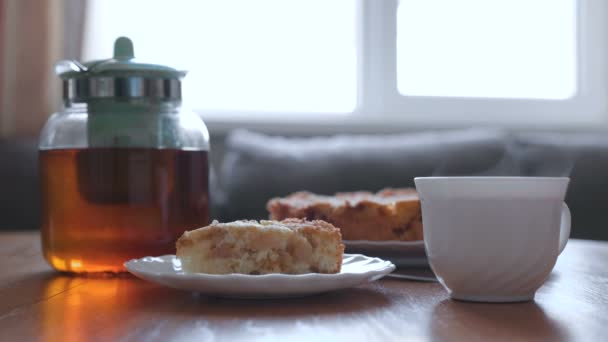 Slice of homemade apple pie and hot tea on the table. Apple pie, teapot and cup of hot tea.