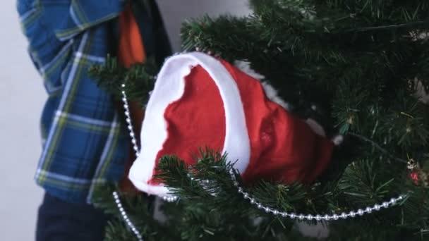 Fiú vegye a kalapját karácsony karácsonyi díszek, és díszíti a karácsonyfát. Közeli kép: kezek.