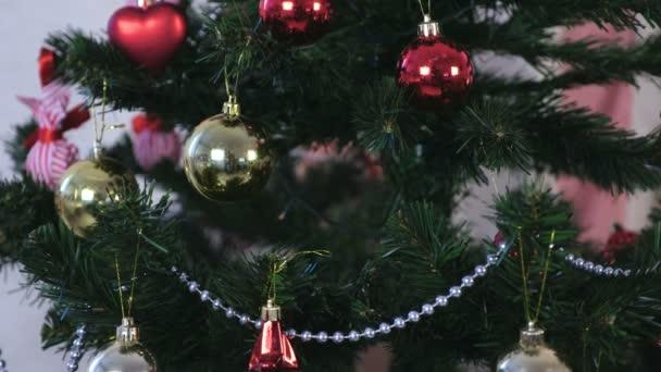 Vánoční dekorace v červené a zlaté a stříbrné korálky na větve vánočního stromku.
