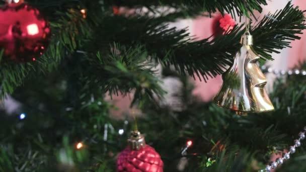 Piros fényes golyó, és arany játékok a karácsonyfa ága. Karácsonyi koszorú a karácsonyfa fények.