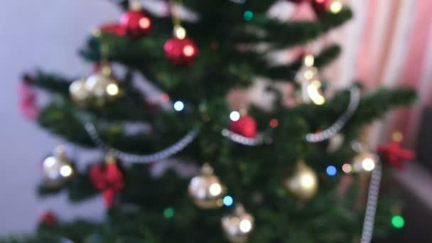 Červené lesklé koule a zlaté hračky na větvích vánočního stromu. Vánoční věnec s osvětlení na vánoční stromeček. Rozostření.