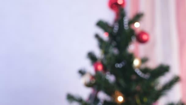 Piros fényes golyó, és arany játékok a karácsonyfa ága. Karácsonyi koszorú a karácsonyfa fények. Blur.
