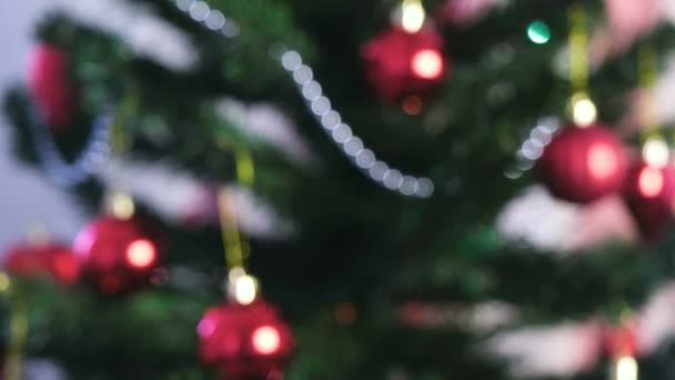 Red shiny balls and gold toys on the branches of Christmas tree. Christmas garland with lights on the Christmas tree. Blur.