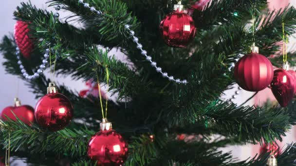 Different balls and gold toys on the branches of Christmas tree. Christmas garland with lights on the Christmas tree.