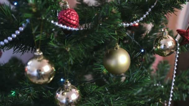 Různé kuličky a zlaté hračky na větvích vánočního stromu. Vánoční věnec s osvětlení na vánoční stromeček.