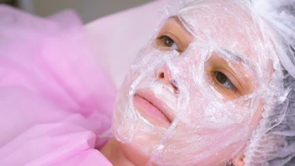 Kosmetikerin legt eine Plastikfolie auf die feuchtigkeitsspendende Maske im Gesicht der Frau.