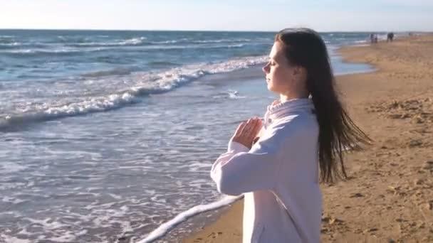 Žena je protahování a dělat jógu Namaste pozice na písčité pláži s vlnami, boční pohled.