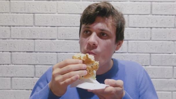 Mann isst lustvoll einen Hamburger im Café.