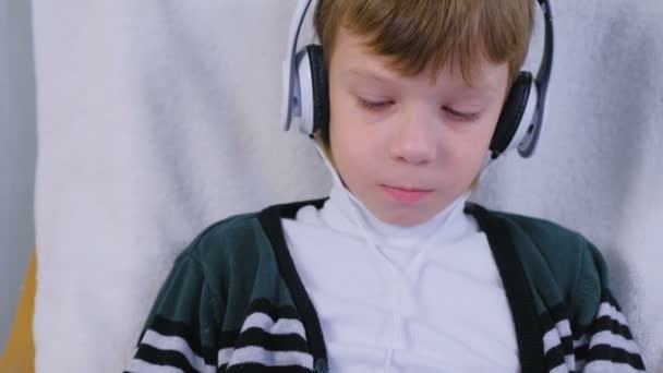 Boy is listening music in headphones sitting in armchair at home.