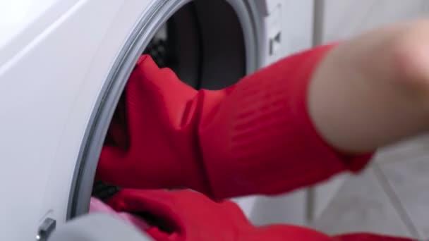 Frau in roten Gummihandschuhen ist eine Waschmaschine mit Schwamm waschen.