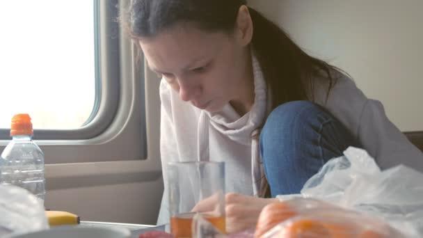 Unavená žena jíst a čtou zprávy na telefonu cestování vlakem v druhé třídy kočár