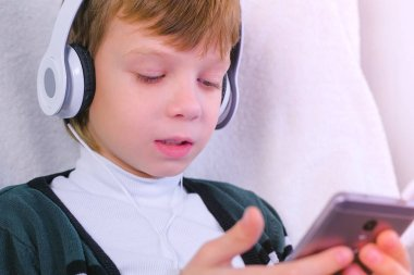 Boy is listening music in headphones in smartphone and singing a song sitting in armchair at home.