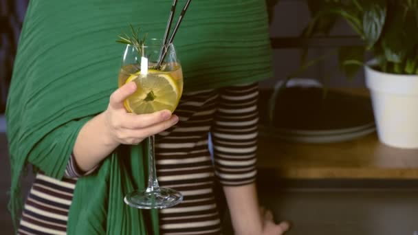 Woman drinks alcohol cocktail in cafe. Hands close-up.