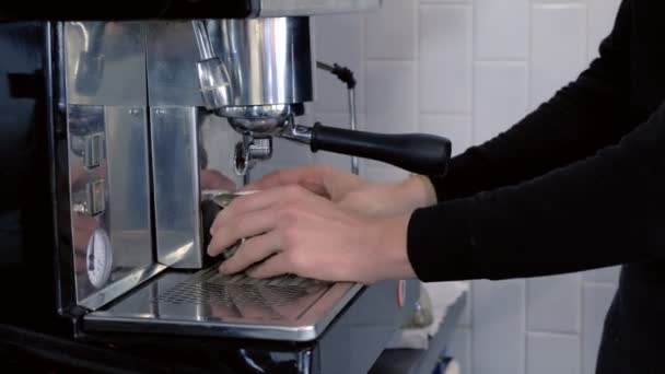 Barista pours espresso to pitcher from coffee machine. Hands close-up.