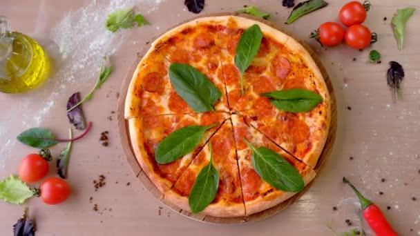 Affettatura di pizza con salame con spinaci foglie sul bordo di legno, primo piano vista dallalto.