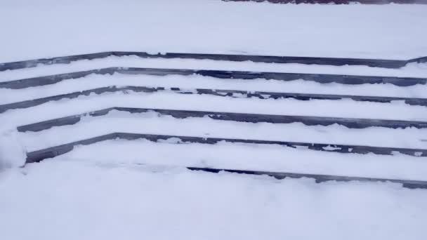 Kroky ve sněhu u vchodu do budovy, v zimě, kluzké schody