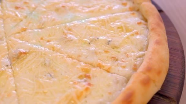 Polovina z krájení pizzy s různými druhy sýrů na dřevěném prkénku zblízka.