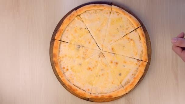 Lidé se plátky pizza Margarita s různými druhy sýrů na dřevěném prkénku detailní pohled shora.