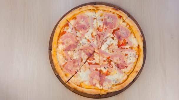 Pizza se slaninou a sýrem na dřevěné desce na stole. Pohled shora detail.