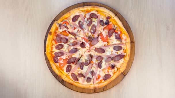 Slicing pizza with smoked sausage, ham and cheese. Close-up view.