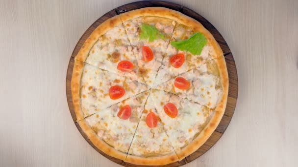 Chef puts tomatoes and lettuce on pizza with chicken and cheese on wooden board. Hands close-up.