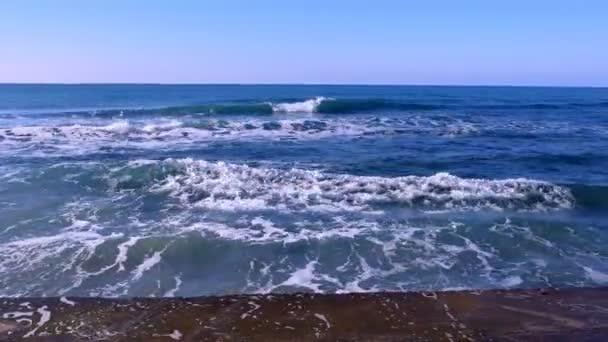 Fröccsenő víz, a viharos hullámok feltörése a móló, a vízparton. Kék clear sky.