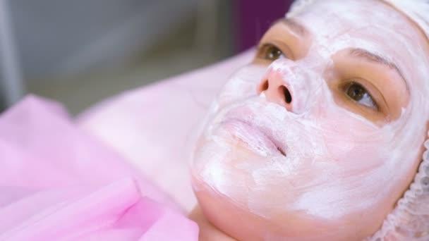Frauengesicht mit feuchtigkeitsspendender Maske auf dem kosmetologischen Eingriff. Nahaufnahme.
