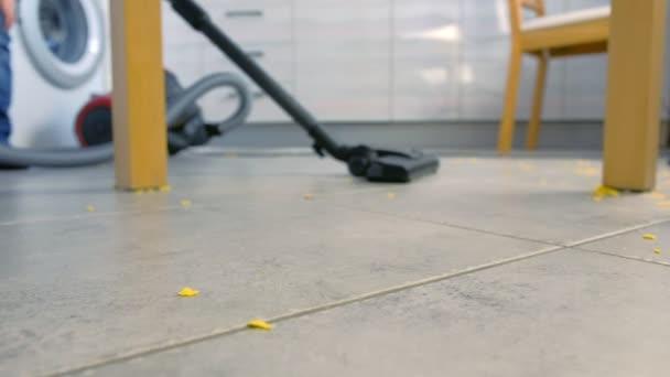 Kind staubsaugt den Küchenboden. Er räumt die auf der grauen Fliese verstreuten Cornflakes auf. Beine aus nächster Nähe.