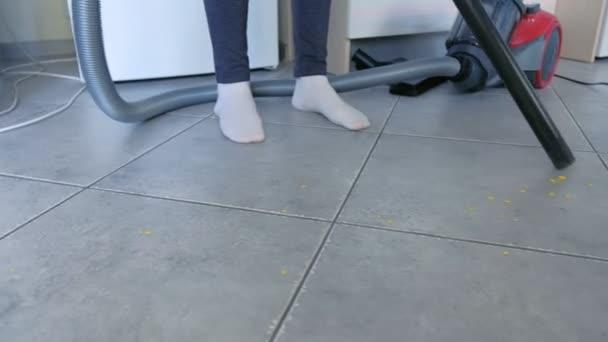 Frau staubsaugt den Küchenboden mit grauer Fliese ohne Bürste, nur Staubsaugerrohr. Beine aus nächster Nähe.